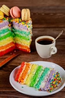 一杯のコーヒーと誕生日のカラフルなレインボーレイヤーケーキ。