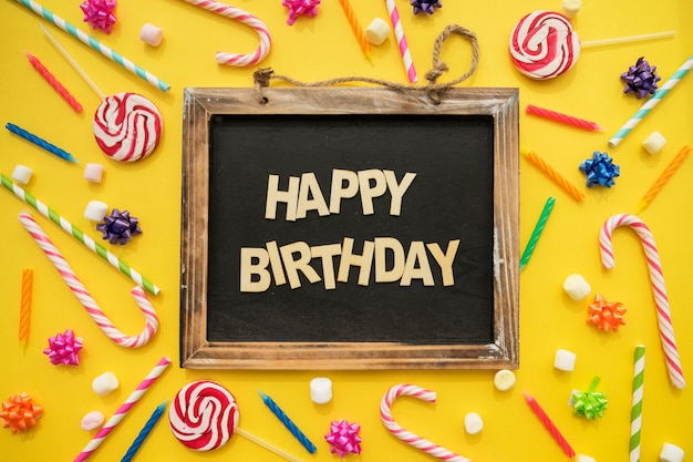 Composizione di compleanno con candele, dolci e ardesia