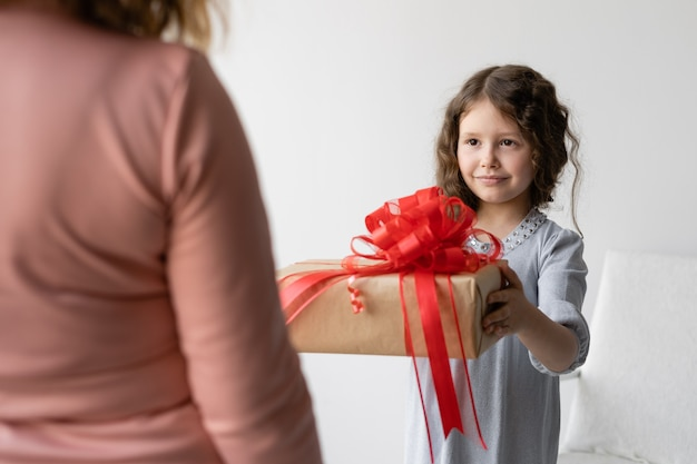 Birthday concept. girl schoolgirl in a blue dress gives her mom a gift.
