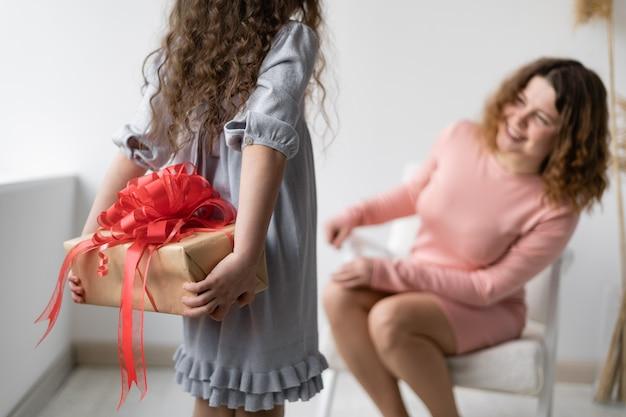 생일 개념. 물결 모양의 머리를 가진 행복 한 젊은 여자는의 자에 앉아있다.