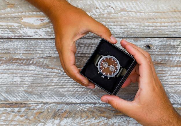 フラット木製の背景に誕生日のコンセプトが横たわっていた。時計ボックスを授受する手。