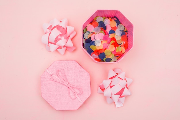 Birthday concept with confetti in gift box, bows on pink background flat lay.