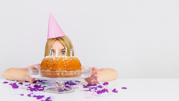 Birthday concept with womans face behind cake