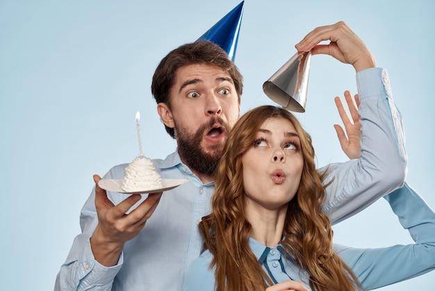 カップケーキと分離されたパーティの帽子を身に着けているキャンドルで誕生日カップル