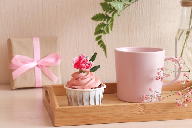 木製トレイに誕生日カップケーキとコーヒーのカップ