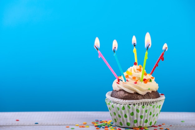Birthday cupcake on blue with multicolor candles.