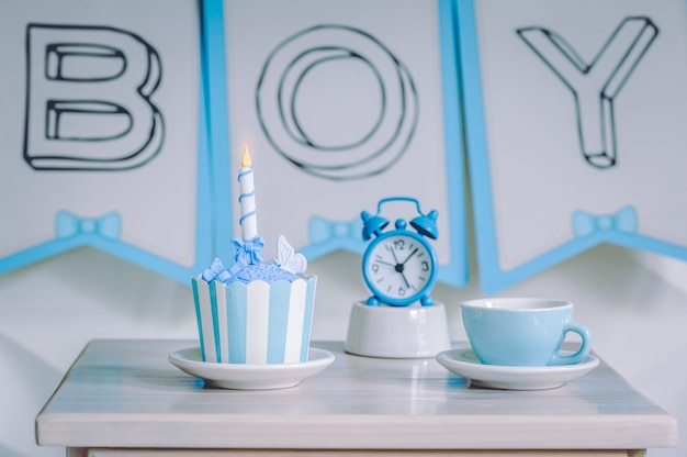 Birthday cupcake dessert with blue alarm clock and cup of tea.