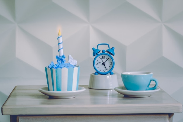 Birthday cupcake dessert with blue alarm clock and cup of tea