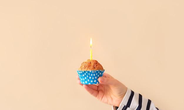 Кекс на день рождения с горящей свечой в руке держит вкусный минимализм с кексами и копирует пространство