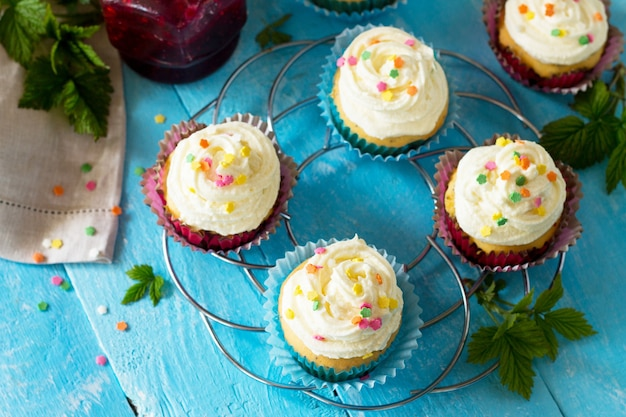 Birthday cupcake with buttercream icing and raspberry jam a wooden table copy space