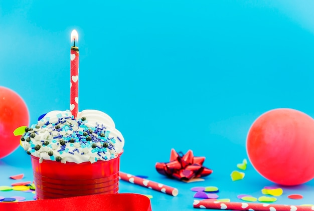 Birthday cupcake with candle and balloons