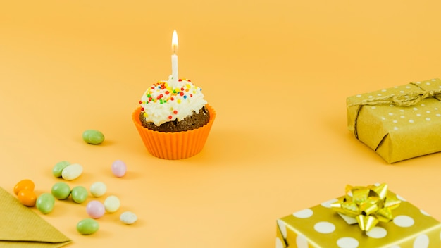 Birthday cupcake with candle and gifts
