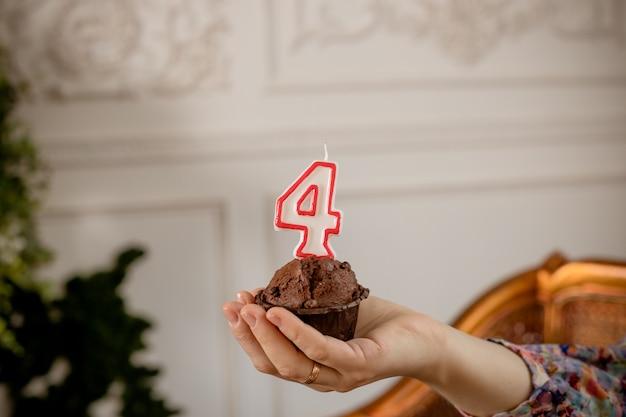 손에 촛불 생일 컵 케 익입니다. 머핀 위에 생일 번호 4 번. 축하 생일 컵케익.