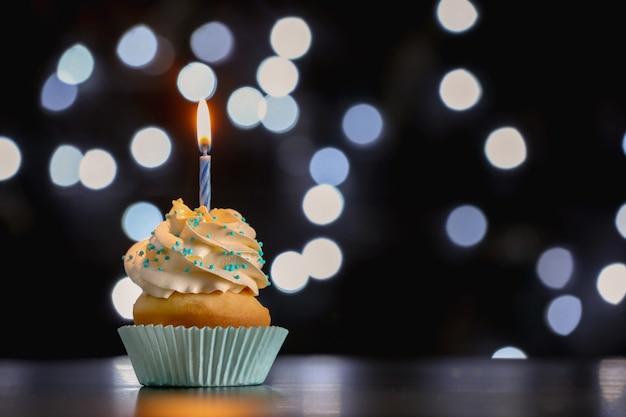 ぼやけた光に対してテーブルの上のキャンドルと誕生日のカップケーキ