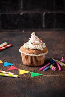 Birthday cupcake with cream and decorations