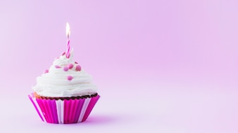 Birthday cupcake with illuminated candle on purple background