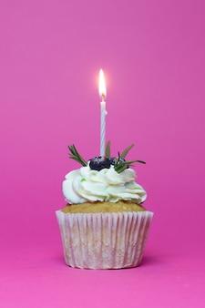 Кекс на день рождения с одной зажженной свечой на розовом фоне