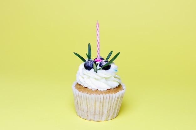 Кекс на день рождения с одной зажженной свечой на желтом фоне