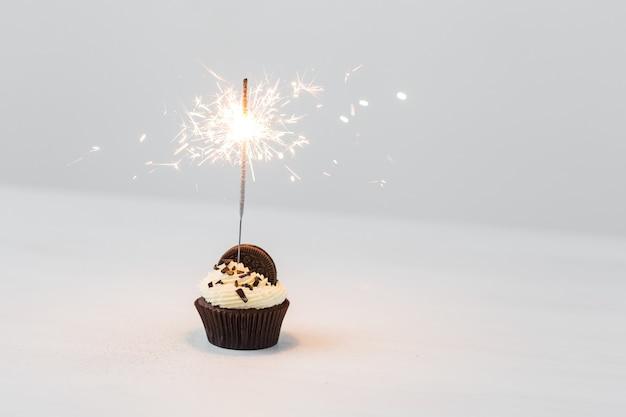 Кекс на день рождения с бенгальским огнем на белой стене с копией пространства