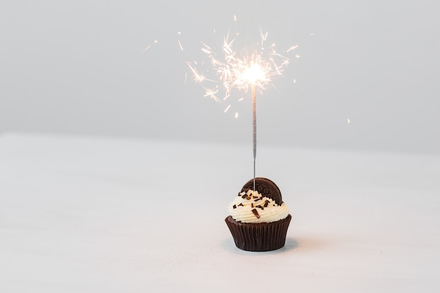 Birthday cupcake with sparkler over white background .