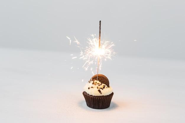 Birthday cupcake with sparkler over white background.