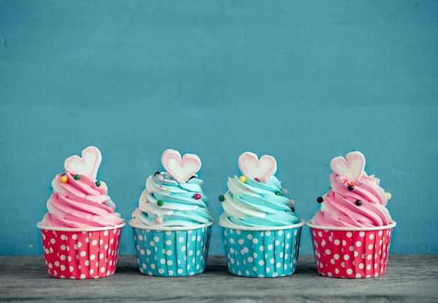 青い背景にマシュマロの甘い心の形の誕生日カップケーキ