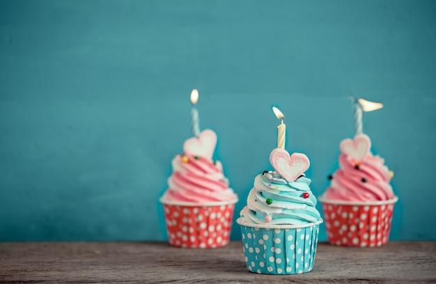 マシュマロと蝋燭の甘い心の形の誕生日カップケーキ、青い背景