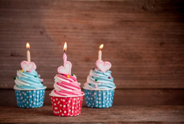 マシュマロと蝋燭の木の背景に甘い心の形の誕生日カップケーキ