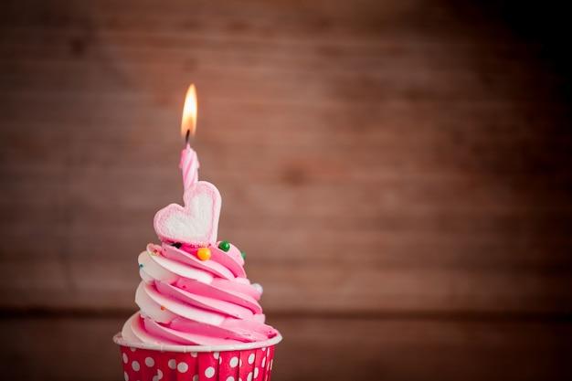 День рождения кекс со сладким сердцем форме зефира и свечи на деревянном фоне