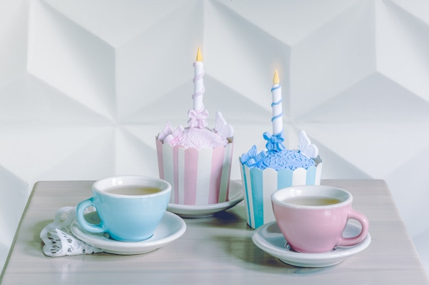 Birthday cupcakes with birthday candle and cups of tea