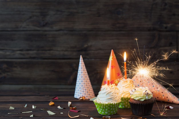 오래 된 어두운 나무 테이블에 초 생일 컵 케이크