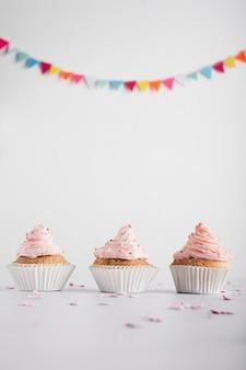 アイシングと花輪の誕生日カップケーキ