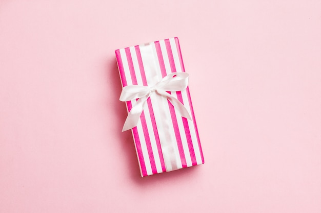 Birthday gift box on pink wrapping paper, top view