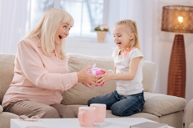 생일 선물. 귀여운 좋은 흥분된 소녀는 소파에 앉아 그녀의 생일 선물에 대해 행복하면서 선물을 가지고