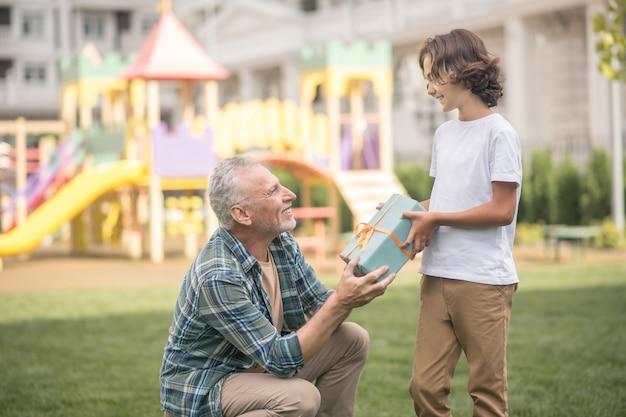 생일 선물. 그의 아들에게 선물 상자를주는 회색 머리 남자
