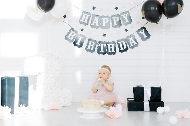 Именинница 1 год сидит в фотозоне в окружении подарков, цветов