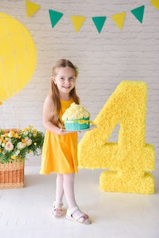 Birthday girl 4-5 years old is celebrating birthday in a decorated stylized studio, number 4 and big balloon. yellow style.