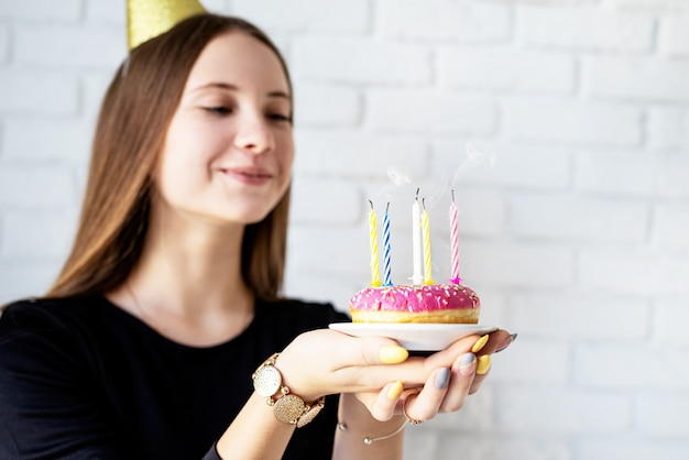 Birthday girl blowing candles on the donut