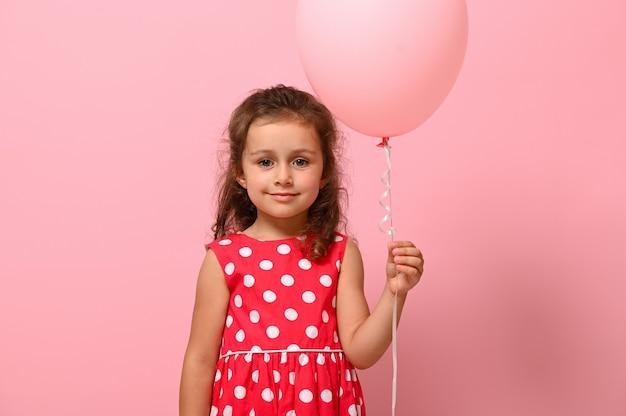 パステルピンクの風船を保持し、笑顔で、コピースペースでピンクの背景の上に分離された水玉模様のドレスに身を包んだ誕生日の女の子。広告のための美しい4歳の子供のクローズアップの肖像画