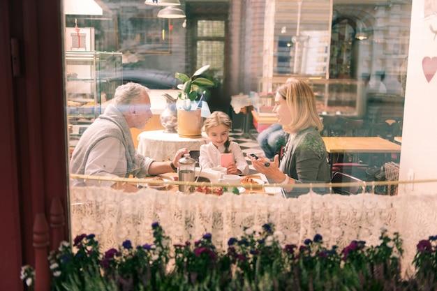 생일 소녀. 생일 소녀를 분위기있는 프랑스 빵집에 데려가는 행복하고 사랑스러운 조부모님