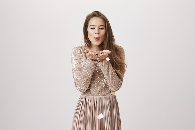 Именинница в вечернем платье дует конфетти от ладоней