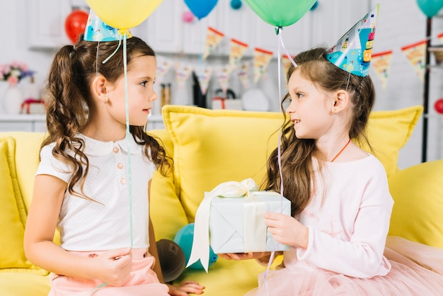 Birthday girl looking at her friend holding presents in hand at birthday party