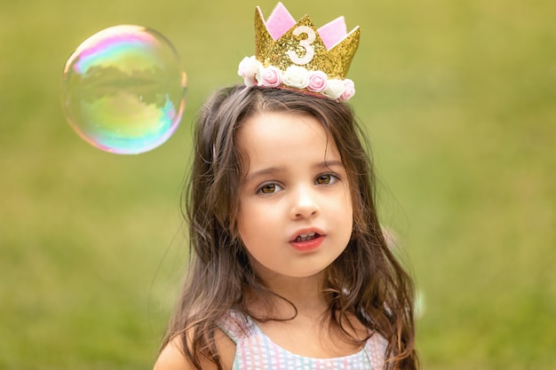 Birthday girl playing with soap bubbles outdoors