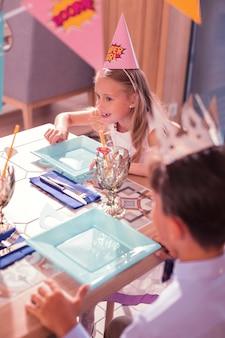 笑顔でテーブルで食べ物を待っている誕生日の女の子