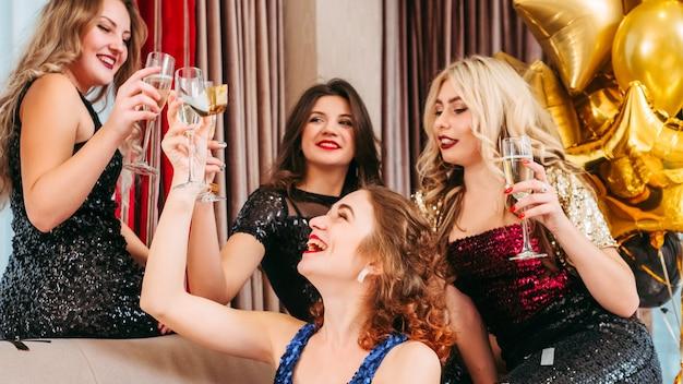 親しい友人と彼女の特別な日を過ごす誕生日の女の子。スパークリングワインとグラスをチリンと鳴らす派手なドレスを着た女性たちが楽しんでいます。