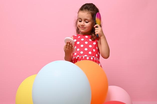 Именинница стоит за разноцветными воздушными шарами, расчесывает вьющиеся волосы расческой, мило улыбается, глядя на свое отражение в маленьком розовом косметическом зеркале, изолированном на розовом фоне с копией пространства