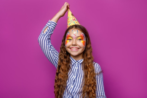 Birthday girl with colorful faceart wear party cap posing isolated on violet wall.