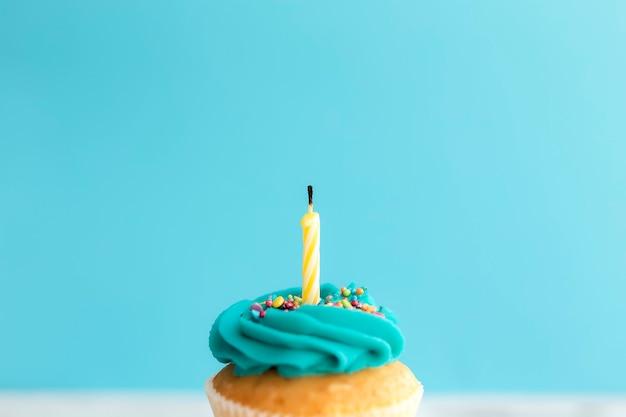 誕生日の挨拶の概念。マフィンやカップケーキにろうそくを吹き消します。