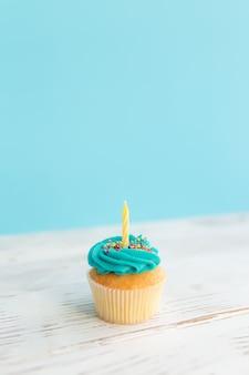 생일 인사말 개념입니다. 머핀 또는 컵 케 익에 노란색 촛불입니다.