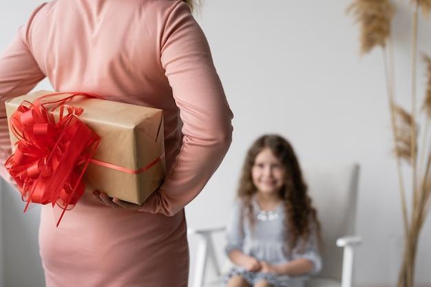 생신. 물결 모양의 머리를 가진 행복 한 어린 소녀는 의자에 앉아 선물을 기다리고 있습니다.